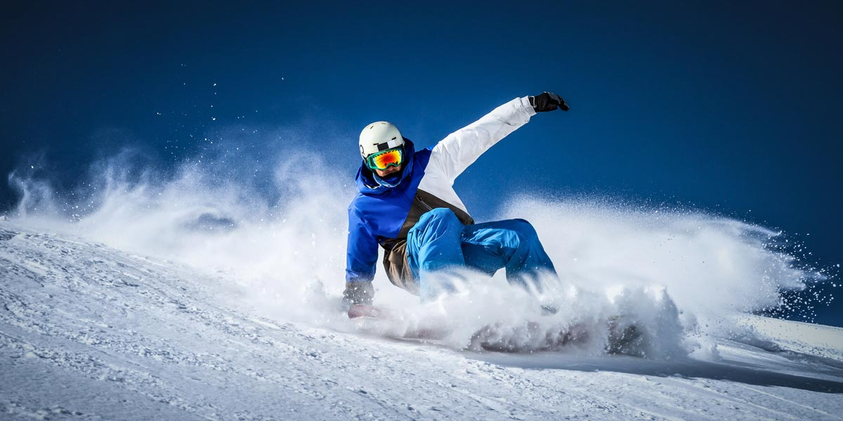 Snowboarder sliding downhill making powder