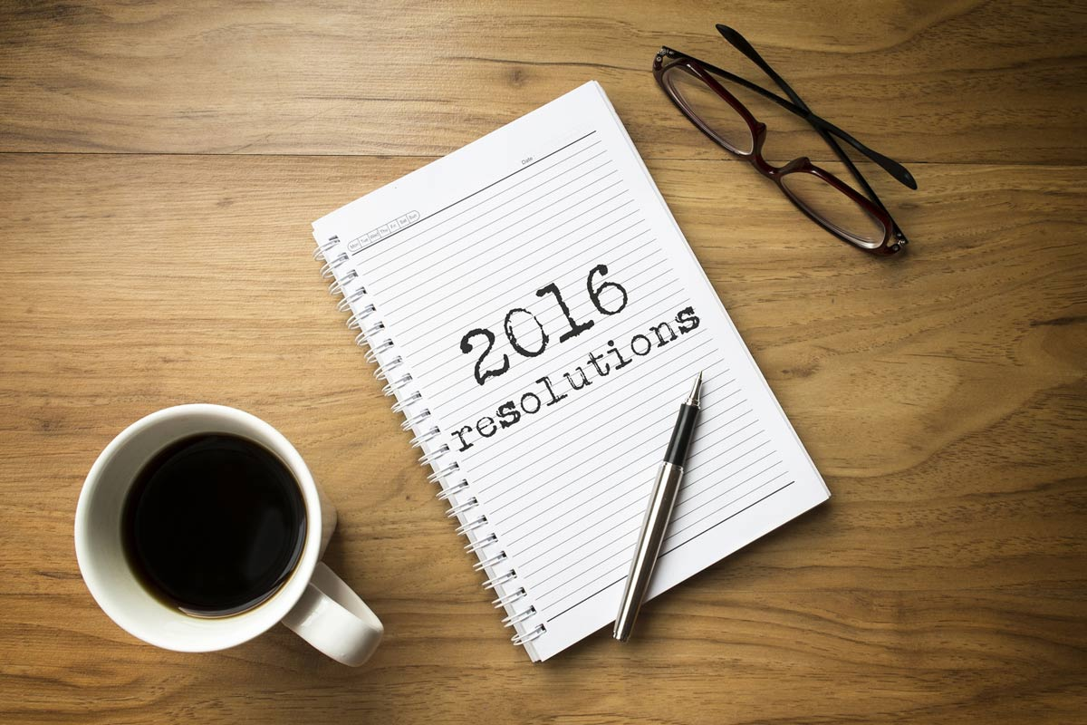 2016 resolutions written on a notepad next to a coffee and glasses