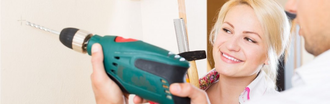 Man doing DIY using a power drill witha woman watching