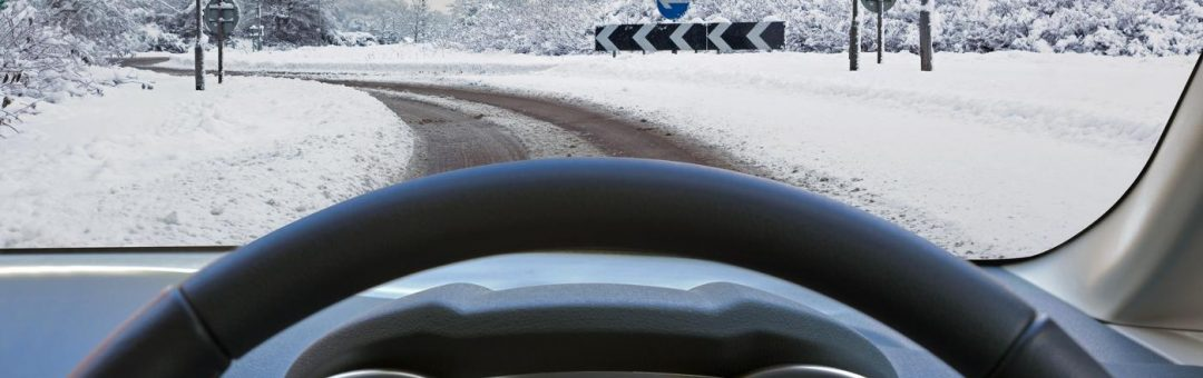 Car drivers view through the vehicle windscreen whilst driving on a snow covered road approaching a roundabout with Give Way signs, the dual carriageway has one driveable lane formed by previous motorists.